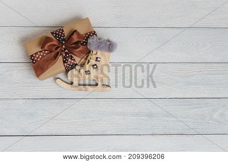 Christmas and New Year holiday background. Close up handmade ornaments of skate and gift box on wooden table, festive decoration and celebration concept. flat lay top view