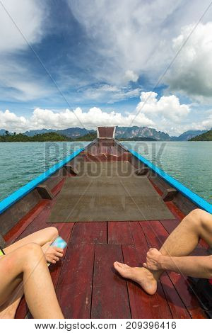 Guy With A Girl On The Nose Of A Long-tailed Boat