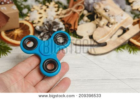 Man Hand holding Spinner on white wooden table with christmas decoration and copyspace