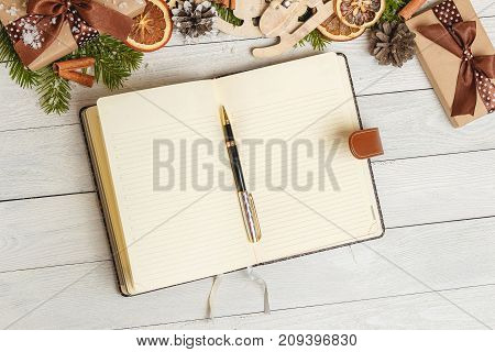 Christmas gifts, Christmas ornaments and an open blank notebook on a light wooden table