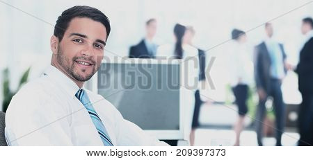 Portrait of smiling businessman working in office, looking camera