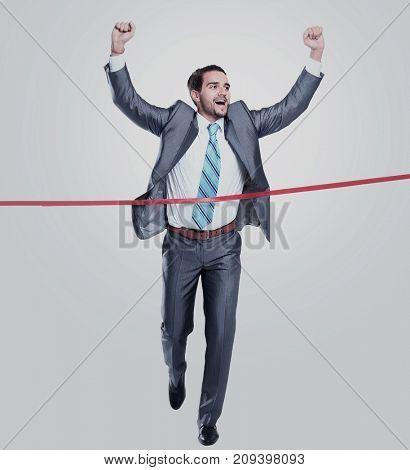 Happy businessman running through finishing line. Isolated on white