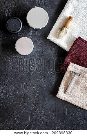At the barbershop. Razors, shaving brush, towel on black background top view.
