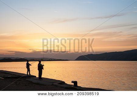 VELIKO GRADISTE SERBIA - SEPTEMBER 16 2017: Fishermen fishing on the quay of Veliko Gradiste at Sunset on the Danube river Picture of two men fishing in the Serbian city of Veliko Gradiste on the Danube river at sunset.