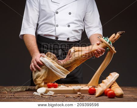 Cook holds a ham in his hands. Spanish jamon, spain traditional bread, tomatoes, spices, onion rings. Horizontal close up image