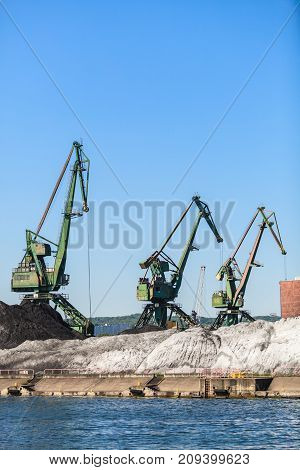Industry equipment technology cargo commerce transport concept. Cranes in morning harbour. Industrial machines working in port facility.