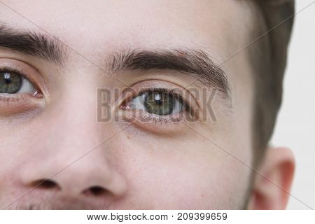 Crop of young man's face looking at camera