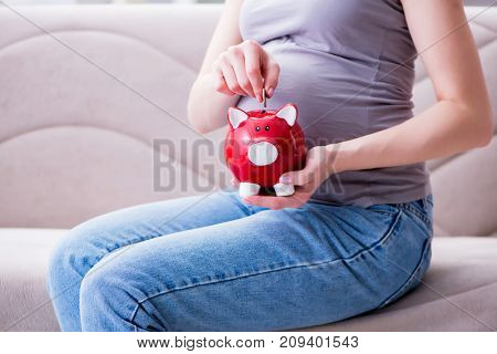 Pregnant woman with a belly tummy sitting on a sofa at home