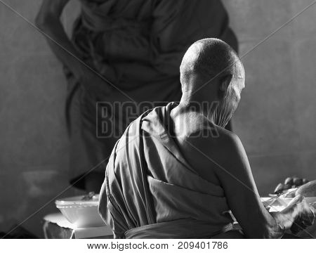 A monk partaking in a daily meal following prayers