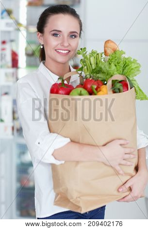 Young woman holding grocery shopping bag with vegetables .Standing in the kitchen. Woman in the kitchen looking at the camera