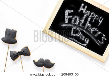 Father's day or birthday celebration with black tie, mustache and hat sign cookies on white desk background flat lay copyspace