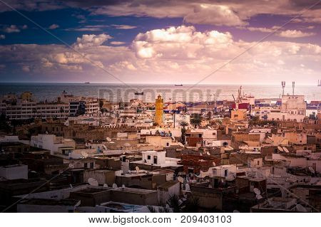View of the Medina and the sea with ships, Tunisia. Cityscape of Sousse at sunset with skies and clouds.