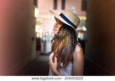 Girl with hat on summer day in the street touching her hair looking aside.