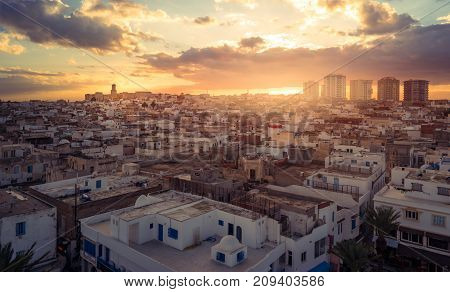 View of the Medina and the castle kasbah in Sousse, with new buildings in distance Tunisia. Cityscape of Sousse at dramatic sunset with red skies and clouds.
