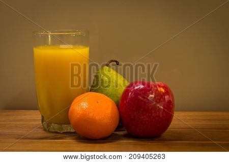 healthy glass of orange juice with apple, mandarin and pear