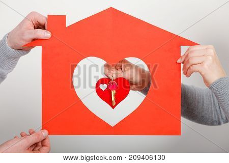 Key to happiness and living together. Love and dream. Woman hand holds little red heart with keys to new home house flat apartment holding by man.
