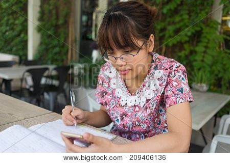 Young girl cheking list on her phone and write down