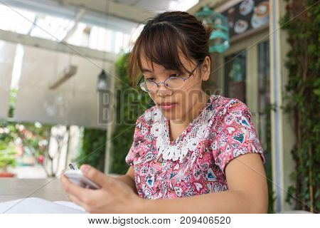 Asian woman checking her mails on the smart phone carefully