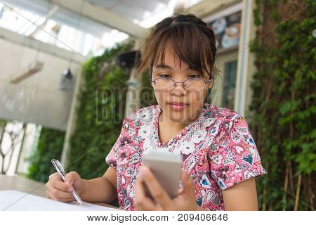 Young girl checking information on the smart phone