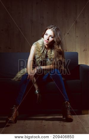 Portrait of elegant woman sitting on black sofa wearing a blue jeans and fur vest