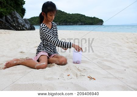 Cigarette and tobacco ashtray on the beach. Volunteer girl collecting butts and garbage on the sand. Marine pollution destructive nature