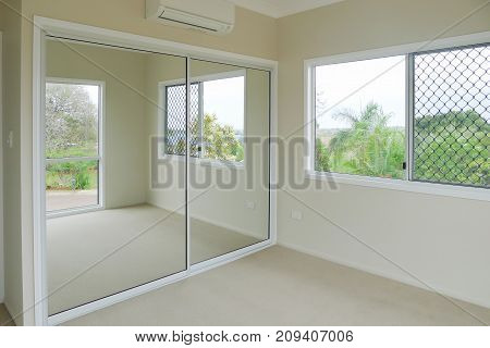 Freshly painted walls in new bedroom with mirror doors, air conditioner and carpet on floor