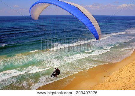 a man flies on a wing along the seashore