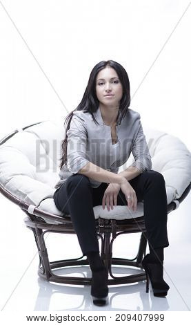 Young woman sitting in a round cozy soft big chair.