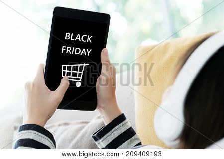 Woman hand using tablet with black Friday sale on screen device background for mock up template technology and lifestyle concept