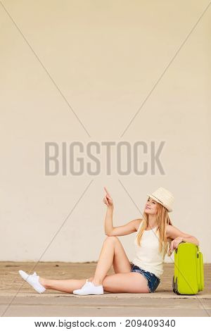 Travel adventure teenage journey concept. Woman wearing denim shorts white top and sun hat suitcase holding suitcase on wheels sitting and pointing at something
