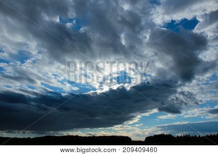Blue sky with cumulus clouds at sunset with forest on the horizon. Landscape
