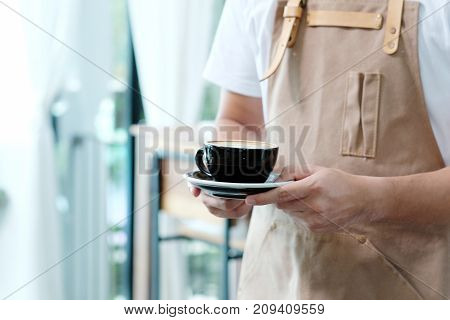 Male barista serving a cupof coffee in the cafe food and drink service concept