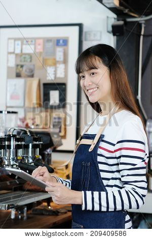 Young asian woman barista using tablet to get coffee order at cafe counter background food and drink concept