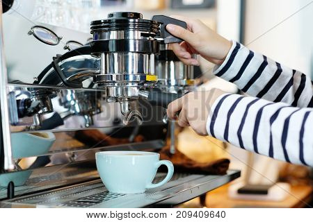 Woman hand using coffee machine at cafe counter food and drink concept
