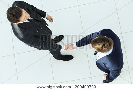 view from the top.handshake, business partners ,isolated on white background.