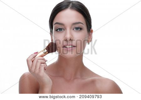 Close-up of a beautiful woman with a make-up brush