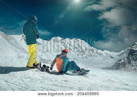 Men and Woman on the snowboards before sport action at sunny day around mountains under blue sky.