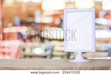 Blank white menu board standing on wood table over blur restaurant with bokeh background space for text mock up product display montage banner