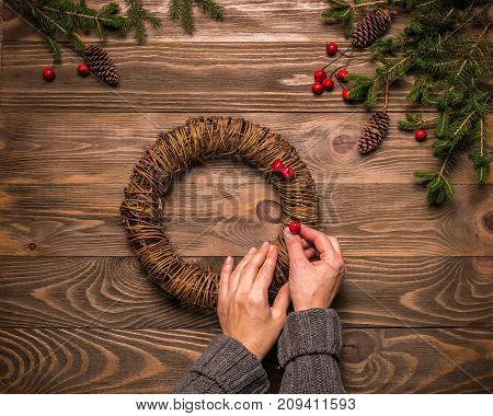 Female hands making Christmas wreath of fir branches. A traditional symbol of Christmas. The festive concept. The view from the top. Dark wooden background.