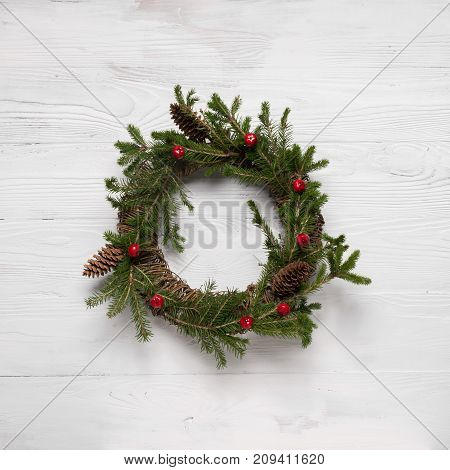 Christmas wreath on white wooden background. A traditional symbol of Christmas. Round frame. The festive concept.The view from the top flat layer. Light wooden background.