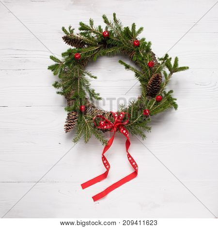 Christmas wreath on white wooden background. A traditional symbol of Christmas. Round frame. The festive concept. The view from the top flat layer. Light wooden background.