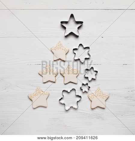 Christmas tree from cookies and different metal shapes on a white wooden background. A traditional symbol of Christmas. The festive concept. The view from the top flat layer. Light wooden background.