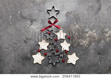Christmas tree from cookies and different metal shapes on a gray background decorated with a red bow and berries . A traditional symbol of Christmas. The festive concept. The view from the top flat layer. The gray backdrop of concrete. A copy of the place