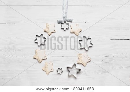 Christmas wreath cookies and various metal shapes on a white wooden background. A traditional symbol of Christmas. The festive concept. The view from the top flat layer. Light wooden background.