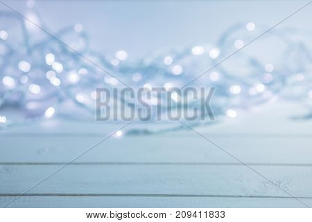 Glowing garland defocused bokeh lights on wooden background