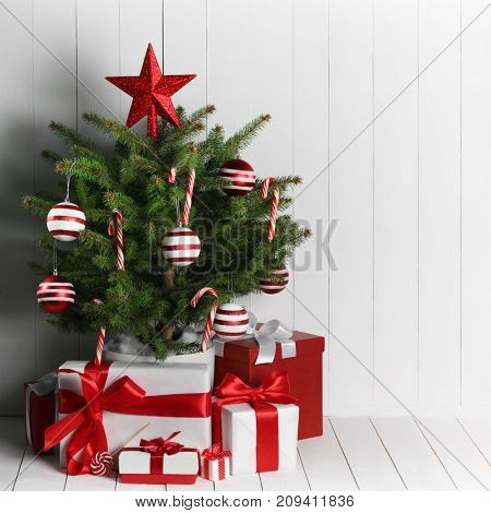 Merry christmas card with decorated christmas tree on white wooden background