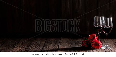 Two glasses of red wine and red roses on dark wooden background, Valentine day