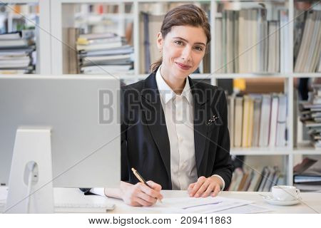 Portrait of smiling businesswoman looking at camera and smiling while working with documents at office in front of computer