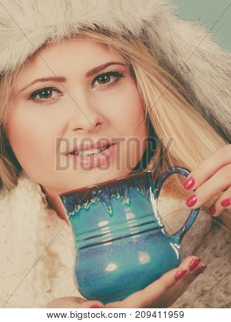 Accessories and clothes for cold days fashion concept. Blonde woman in winter warm furry hat in russian style and scarf drinking hot drink from mug.