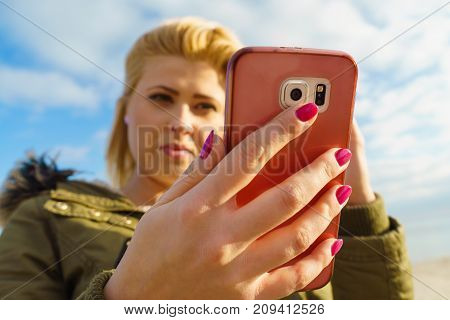 Social media technology modern devices internet concept. Woman teenager wearing warm coat using her smartphone while walking outside on sunny day sky with clouds in background